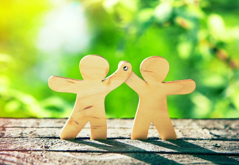 Two wooden figures high-fiving each other  - learn the difference between counselling and psychotherapy with Sarah Tuckett Psychotherapy and Counselling North Brisbane