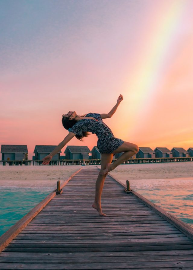 Woman dancing in front of a rainbow - somatic movement therapy with Sarah Tuckett Psychotherapy and Counselling North Brisbane