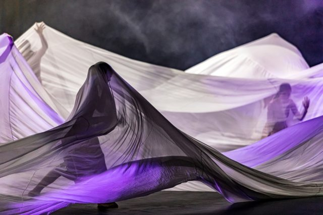 Women dancing under silk sheet