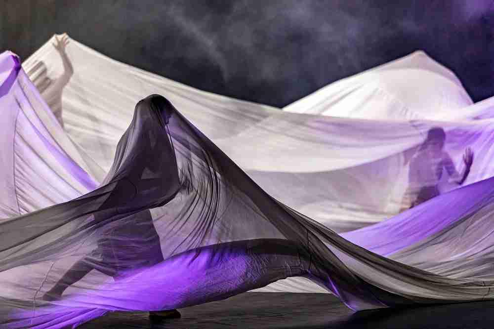 Women dancing under silk sheet