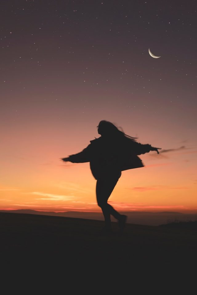 Young woman dancing at sunset - somatic movement therapy with Sarah Tuckett Psychotherapy and Counselling North Brisbane